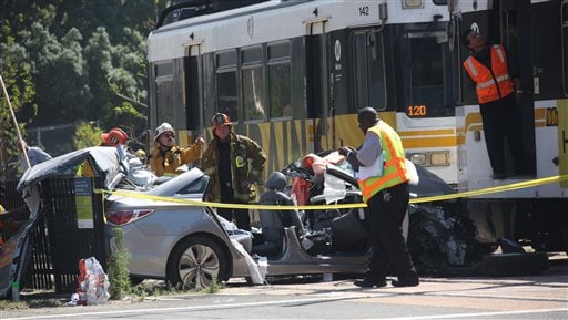 Emergency personnel work at the site of a collision between and Expo Line commuter train and a vehicle near downtown Los Angeles on March 28, 2015. (AP Photo/Los Angeles Times, Irfan Khan)