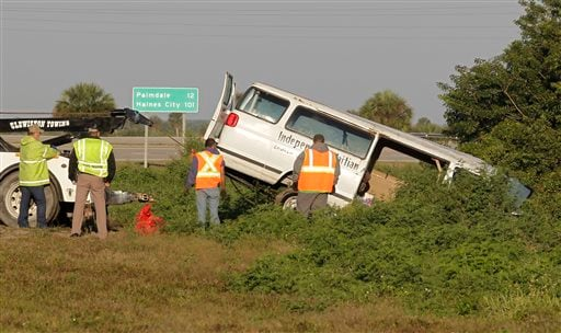 Workers pull a van out of a canal at the intersection of US 27 and State Road 78 West, Monday, March 30, 2015, near Moore Haven, Fla. (AP Photo/Luis M. Alvarez)
