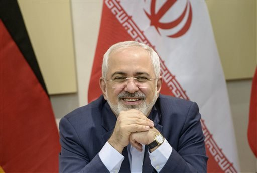 Iranian Foreign Minister Javad Zarif smiles before a meeting on Iran's nuclear program with Britain, Russia, China, France, Germany, European Union and the U.S. officials at the Beau Rivage Palace Hotel in Lausanne, Switzerland Monday, March 30, 2015. Neg