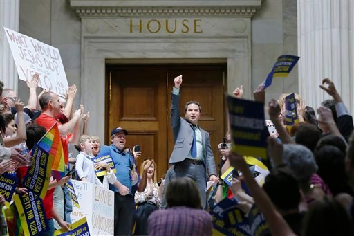 Rep. Warwick Sabin, D-Little Rock, center, cheers with protesters outside of the House chamber at the Arkansas state Capitol in Little Rock, Ark., Monday, March 30, 2015. (AP Photo/Danny Johnston)