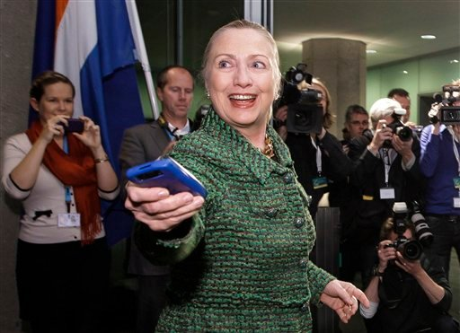 Dec. 8, 2011, file photo: Then-U.S. Secretary of State Hillary Clinton hands off her mobile phone after arriving to meet with Dutch Foreign Minister Uri Rosenthal at the Ministry of Foreign Affairs in The Hague. (AP Photo/J. Scott Applewhite, Pool/File)