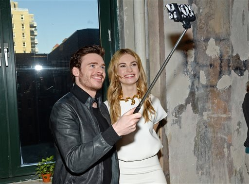 "In this March 9, 2015 file photo, actors Richard Madden and Lily James take a selfie while attending AOL's BUILD Speaker Series to discuss their new film ""Cinderella"" at AOL Studios in New York City."