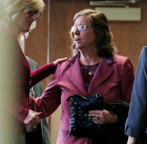 In this file photograph taken on Monday, Dec. 8, 2014, an unidentified woman, left, consoles Arlene Holmes, right, as she leaves the courtroom after a pre-trial readiness hearing in Centennial, Colo., in the murder trial of her son, James Holmes, who is c