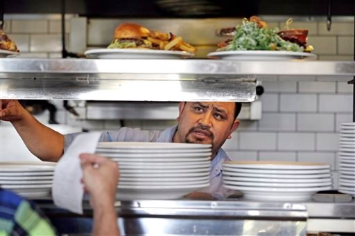 In this photo taken Tuesday, March 31, 2015, cook Alex Romero looks out from the kitchen at the Skillet Diner in Seattle. (AP Photo/Elaine Thompson)