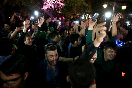 Iranians celebrate a framework agreement on Iran's nuclear program between their country and six world powers, in a street in Tehran, Iran, Friday, April 3, 2015. For the second consecutive night in Tehran, hundreds of Iranians celebrated the deal in majo