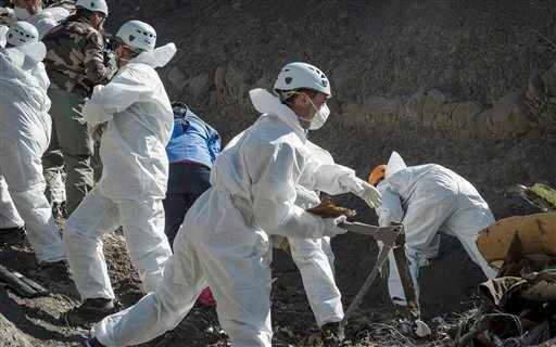 In this photo provided Friday April 3, 2015 by the French Interior Ministry, French emergency rescue services work among debris of the Germanwings passenger jet at the crash site near Seyne-les-Alpes, France. The co-pilot of the doomed Germanwings flight