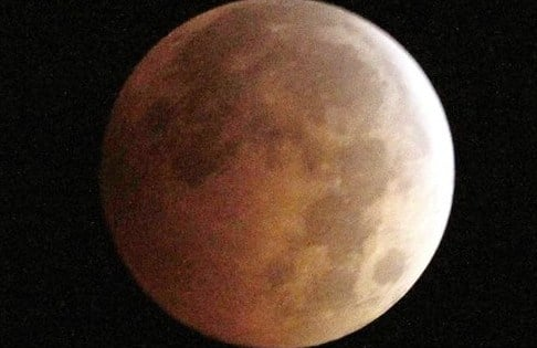 This Oct. 8, 2014, file photo, shows the Blood Moon, created by the full moon passing into the shadow of the earth during a total lunar eclipse, as seen from Monterey Park, Calif. Skygazers in the western U.S. and Canada will be treated to a total eclipse