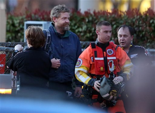 Louis Jordan, second from left, walks from the Coast Guard helicopter to the Sentara Norfolk General Hospital in Norfolk, Va., after being found off the North Carolina coast, Thursday, April 2, 2015. His family says he sailed out of a marina in Conway, S.