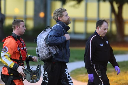 Louis Jordan, center, walks from the Coast Guard helicopter to the Sentara Norfolk General Hospital in Norfolk, Va., after being found off the North Carolina coast, Thursday, April 2, 2015. His family says he sailed out of a marina in Conway, S.C., on Jan