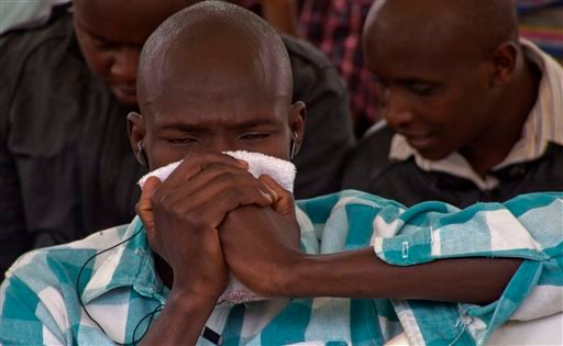 A man holds a cloth to his face as he waits to view the body of a relative killed in Thursday's attack on a university, at Chiromo funeral home, Nairobi, Kenya, Saturday, April 4, 2015. Al-Shabab gunmen rampaged through a university in northeastern Kenya