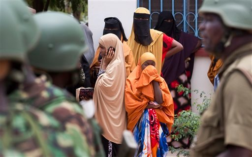 Women look across as Kenya Defence Forces (KDF) soldiers arrive at a hospital to escort the bodies of the attackers to be put on public view, in Garissa, Kenya Saturday, April 4, 2015. Authorities displayed the bodies of the alleged attackers involved in