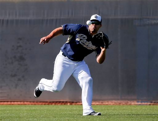 In this March 23, 2015, file photo, San Diego Padres left fielder Carlos Quentin runs down a line drive during fielding drills for outfielders prior to a spring training baseball game against the Chicago White Sox in Peoria, Ariz. In a trade announced Su