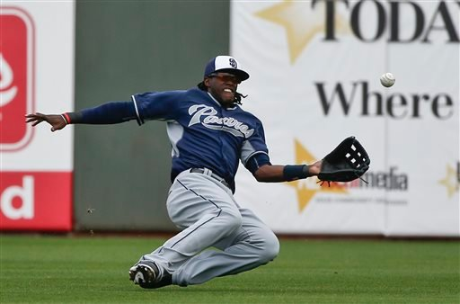 In this March 11, 2015, file photo, San Diego Padres center fielder Cameron Maybin makes the sliding catch on a hit by Kansas City Royals' Ryan Roberts in the third inning of a spring training baseball game in Surprise, Ariz. In a trade announced Sunday,
