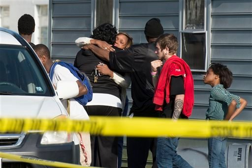 Onlookers gather outside of a house, where police say seven children and one adult have been found dead Monday, April 6, 2015, in Princess Anne, Md.