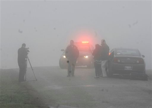 Emergency personnel and media gather at the scene near Bloomington, Ill., where a small plane, with at least five on board, crashed early April 7, 2015. (AP Photo/The Pantagraph, David Proeber)
