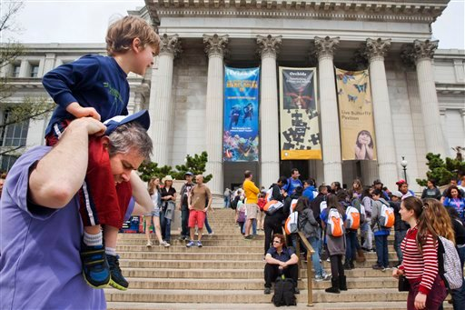 Chris Cellini of Charlotte, N.C., left, lifts his son Aiden Cellini, 5, onto his shoulders after a visit to the Natural History Museum on the National Mall in Washington, Tuesday, April 7, 2015. Widespread power outages affected the White House, State Dep