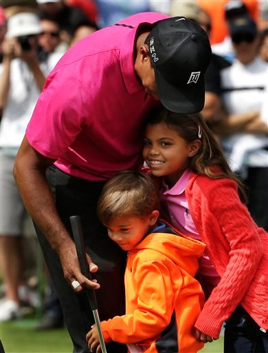 Tiger Woods hugs his children Charlie, left and Sam during a practice round for the Masters golf tournament Tuesday, April 7, 2015, in Augusta, Ga.