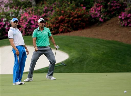 Sergio Garcia, left, of Spain, watches as Jason Day, of Australia, reacts after missing an eagle putt on the 13th hole during the first round of the Masters golf tournament Thursday, April 9, 2015, in Augusta, Ga.