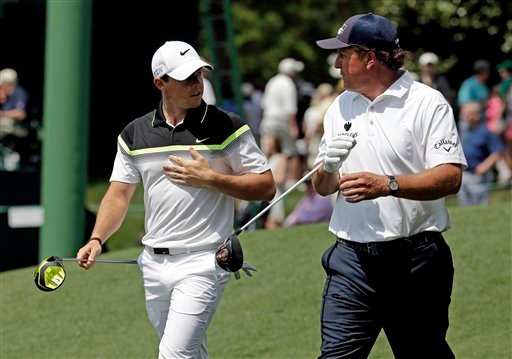 Rory McIlroy, of Northern Ireland, walks down the ninth fairway with Phil Mickelson, right, during the first round of the Masters golf tournament Thursday, April 9, 2015, in Augusta, Ga.