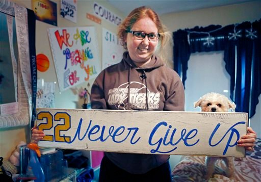n this Dec. 8, 2014, file photo, Lauren Hill holds a sign made for her, which she keeps in her room, along with many other messages and gifts of support.