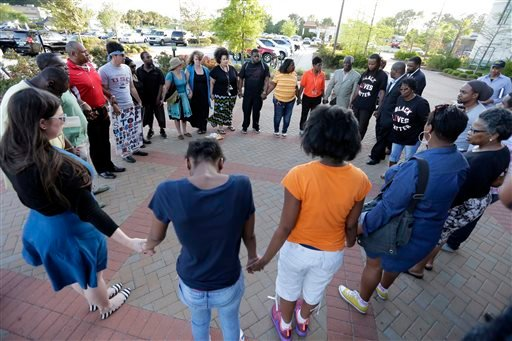People hold hands in prayer during a rally for the killing of Walter Scott by a North Charleston police officer Saturday, after a traffic stop in North Charleston, S.C., Thursday, April 9, 2015. The officer, Michael Thomas Slager, has been fired and charg