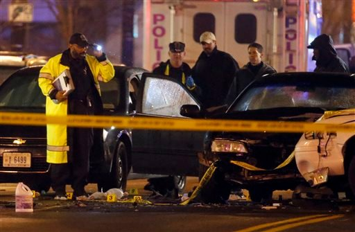 Law enforcement officers investigate the scene involving at least one wrecked DC Metro police car Thursday, April 9, 2015, in Washington. An armed man kidnapped a woman, shot a Census Bureau guard and led police on a car chase through Maryland and Washing