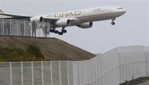 In this Saturday, March 14, 2015 photo, a high fence, bottom, surrounds the Narita International Airport as people enjoy watching a plane of the United Arab Emirates' Etihad Airways landing from a viewing spot at Shinonomenooka Park in Narita, east of Tok