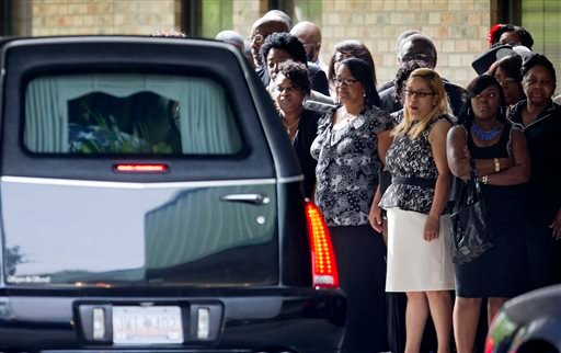 Mourners look on as a hearse carrying the casket of Walter Scott arrives for his funeral at W.O.R.D. Ministries Christian Center, Saturday, April 11, 2015, in Summerville, S.C. Scott was killed by a North Charleston police officer after a traffic Saturday