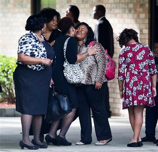Mourners embrace before the funeral of Walter Scott at W.O.R.D. Ministries Christian Center, Saturday, April 11, 2015, in Summerville, S.C. Scott was killed by a North Charleston police officer after a traffic Saturday, April 4, 2015. The officer, Michael