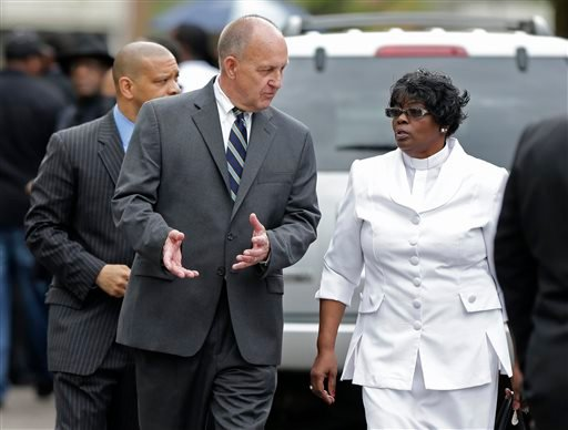 Charleston County Sheriff Al Cannon, center, talks to a woman as he arrives at the World Outreach Revival Deliverance Ministries Christian Center before the funeral service in Summerville, S.C., Saturday, April 11, 2015 for Walter Scott, who was killed by
