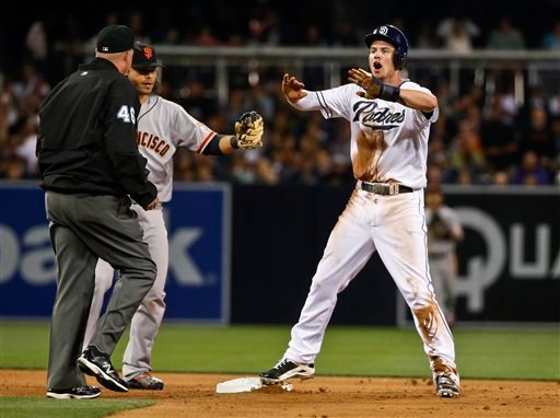 San Diego Padres' Wil Myers protests being called out while trying to steal second in the fifth inning as San Francisco Giants shortstop Brandon Crawford holds up the ball for umpire Ron Kulpz during a baseball game Friday, April 10, 2015, in San Diego. (