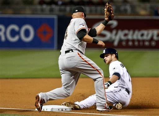 San Diego Padres' Cory Spangenberg slides safely into third as San Francisco Giants third baseman Casey McGehee takes in alate throw in the first inning of a baseball game Friday, April 10, 2015,in San Diego. Spangenberg went from first to third on an inf