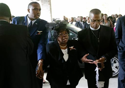 Judy Scott, center, is escorted in for the funeral of her son, Walter Scott, at W.O.R.D. Ministries Christian Center, Saturday, April 11, 2015, in Summerville, S.C. Scott was killed by a North Charleston police officer after a traffic Saturday, April 4, 2