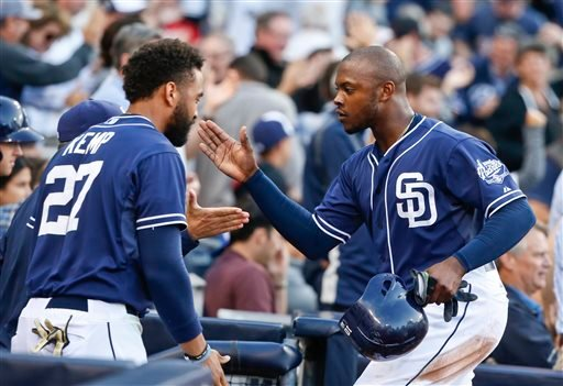 San Diego Padres' Justin Upton, right, is congratulated at the dugout by Matt Kemp and others after scoring against the San Francisco Giants during the third inning of a baseball game Saturday, April 11, 2015, in San Diego. (AP Photo/Lenny Ignelzi)