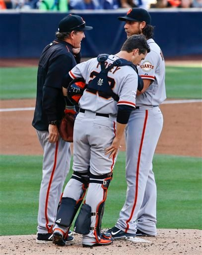 San Francisco Giants starting pitcher Madison Bumgarner gets a visit from pitching coach Dave Righetti and catcher Buster Posey after surrendering two runs in the first inning to the San Diego Padres in a baseball game Saturday, April 11, 2015, in San Die