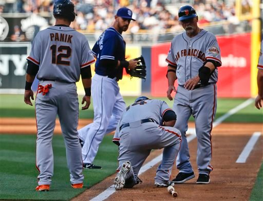 San Francisco Giants' Casey McGehee collapses after straining his knee while trying to run out a fly ball in the first inning of a baseball game against the San Diego Padres, Saturday, April 11, 2015, in San Diego. (AP Photo/Lenny Ignelzi)