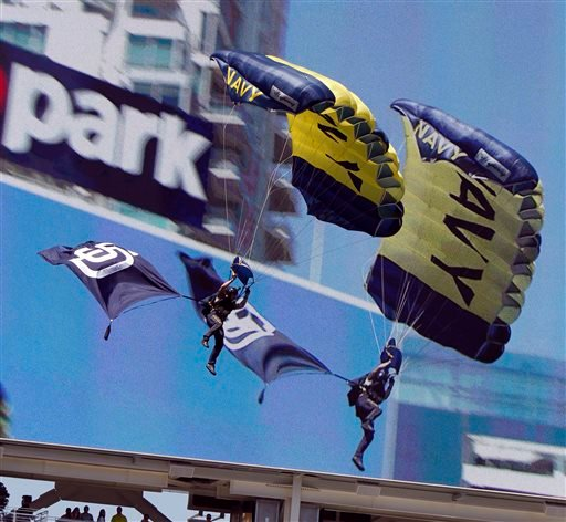 A member of the U.S. Navy Parachute team, know as Leap Frogs, flies down in front of the big screen prior to a baseball game between the San Diego Padres and the San Francisco Giants in San Diego, Calif., Sunday, April 12, 2015. (AP Photo/Alex Gallardo)