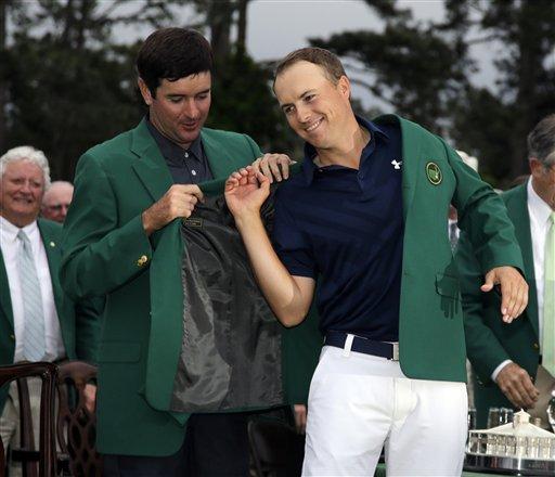 Bubba Watson helps Jordan Spieth put on his green jacket after winning the Masters golf tournament Sunday, April 12, 2015, in Augusta, Ga. (AP Photo/Matt Slocum)