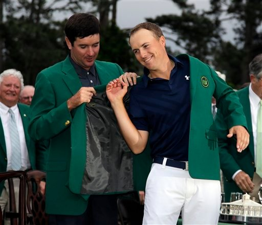 Bubba Watson helps Jordan Spieth put on his green jacket after winning the Masters golf tournament Sunday, April 12, 2015, in Augusta, Ga. (AP Photo/Matt Slocum)