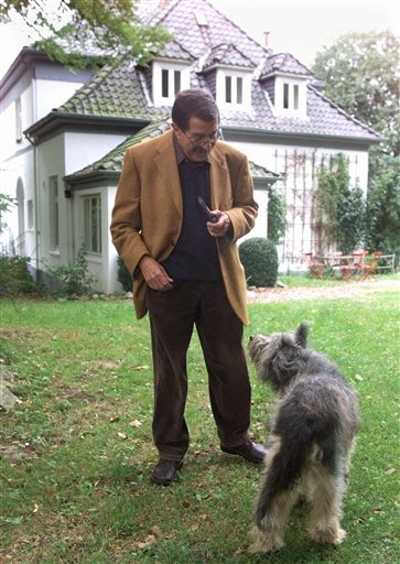 In this Sept. 30, 1999 file photo German writer Guenter Grass talks to his dog Kara outside his house in Behlendorf, northern Germany, after learning that he won the Nobel prize in literature. Nobel laureate Grass has died his publishing house confirmed M