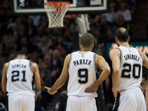 Spurs guards Tony Parker (9), of France, and Manu Ginobili (20), of Argentina, talk on the court as Spurs forward Tim Duncan shoots a free throw during the first half of an NBA basketball game against the Warriors April 5, 2015. (AP Photo/Darren Abate)