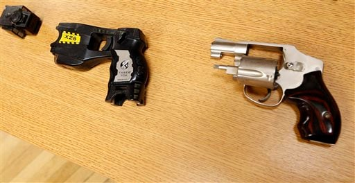 In this Friday, April 10, 2015, photo, a Taser and handgun, similar to the weapons in possession of Tulsa County reserve deputy Robert Bates during a pursuit of Eric Harris, are displayed in Tulsa, Okla. Police say Bates thought he was holding a Taser, no