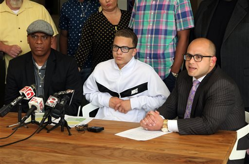 In this Thursday, April 9, 2015 photo, attorney Dan Smolen, right, speaks alongside Andre Harris, Eric Harris' brother, left, and Aidan Fraley, Eric Harris' son, during a news conference at the attorneys' office of Smolen, Smolen and Roytman about Eric Ha
