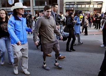 © Boston Marathon survivor Jeff Bauman, right, walks past one of two blast sites with Carlos Arredondo, who helped save his life.