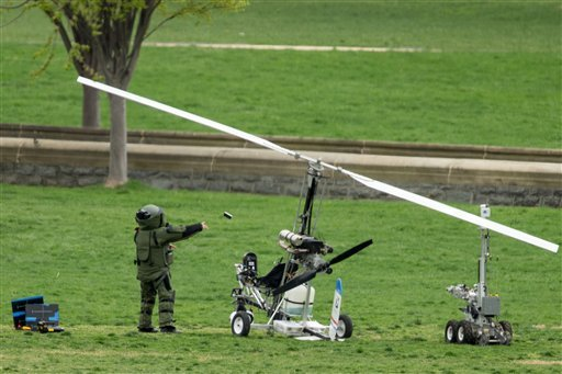 A member of a bomb squad pulls something off of a small helicopter and throws it after a man landed on the West Lawn of the Capitol in Washington, Wednesday, April 15, 2015.