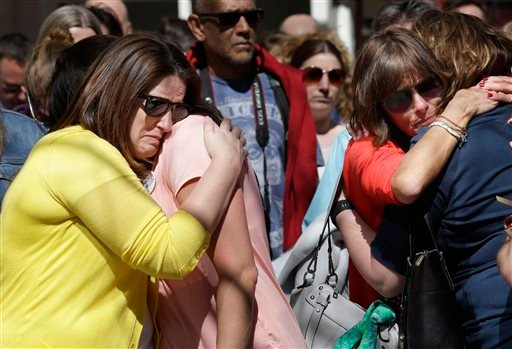Jenna Dziedzic, of Boston, left, hugs Sabrina Dellorusso, also of Boston, second from left, as Linda Witt, of Neenah, Wis., second from right, hugs Jillian Boynton, of Manchester, N.H., right, during a moment of silence at one of two blast sites near the