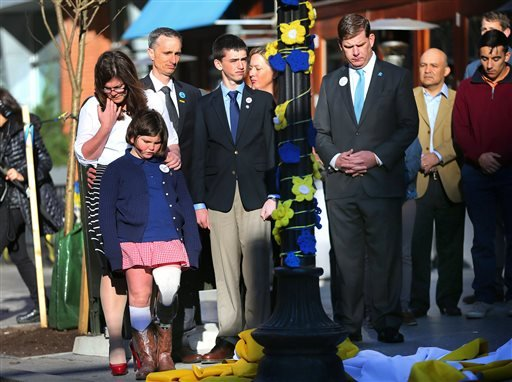 Boston Mayor Marty Walsh, right. looks down after Boston Marathon survivor Jane Richard, left, and her brother Henry removed a drape covering a memorial honoring victims and survivors at one of two blast sites near the finish line of the Boston Marathon i