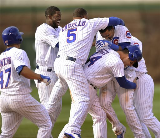 Chicago Cubs' David Ross (3), Welington Castillo (5), Anthony Rizzo (44), Dexter Fowler (24), and Miguel Montero (47), celebrate with teammate Starlin Castro (13), after Castro hit a walk off single to defeat the San Diego Padres 7-6 after eleven innings