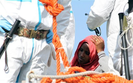 In this picture taken on Tuesday, April 14, 2015 a woman waits to disembark from an Italian Navy vessel in the harbor of Reggio Calabria, southern Italy. The precise number of migrants who have perished in the Mediterranean sea as they flee poverty, war a
