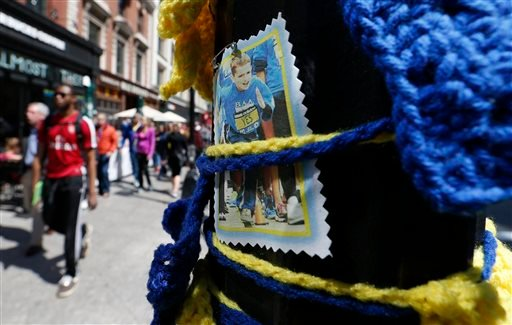 Pedestrians pass a photograph of Boston Marathon bombing victim Martin Richard, Saturday, April 18, 2015, in Boston, at the spot where the second bomb detonated at the marathon in 2013. The 119th Boston Marathon will be run on Monday. (AP Photo/Michael Dw